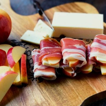 sliced apples and sharp cheddar cheese wrapped with slices of proscuitto ham on a cutting board with a block of cheese in the background