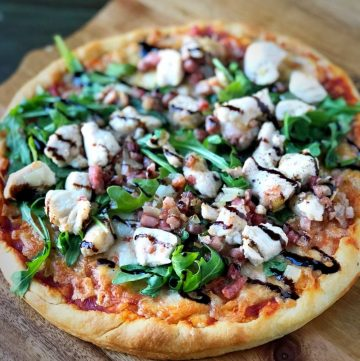 a whole pizza on a cutting board topped with arugula, diced chicken, pancetta, and balsamic glaze