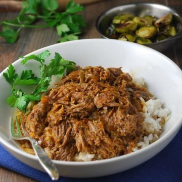 shredded Cuban beef roast in a bowl over rice with fresh herbs and Brussels sprouts in the background