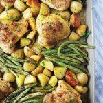 roasted chicken with potatoes and green beans in a sheet pan topped with fresh parsley