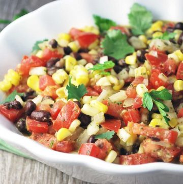 close up of a bowl of mojo salad with corn, black beans, tomatoes, fresh herbs, and dressing