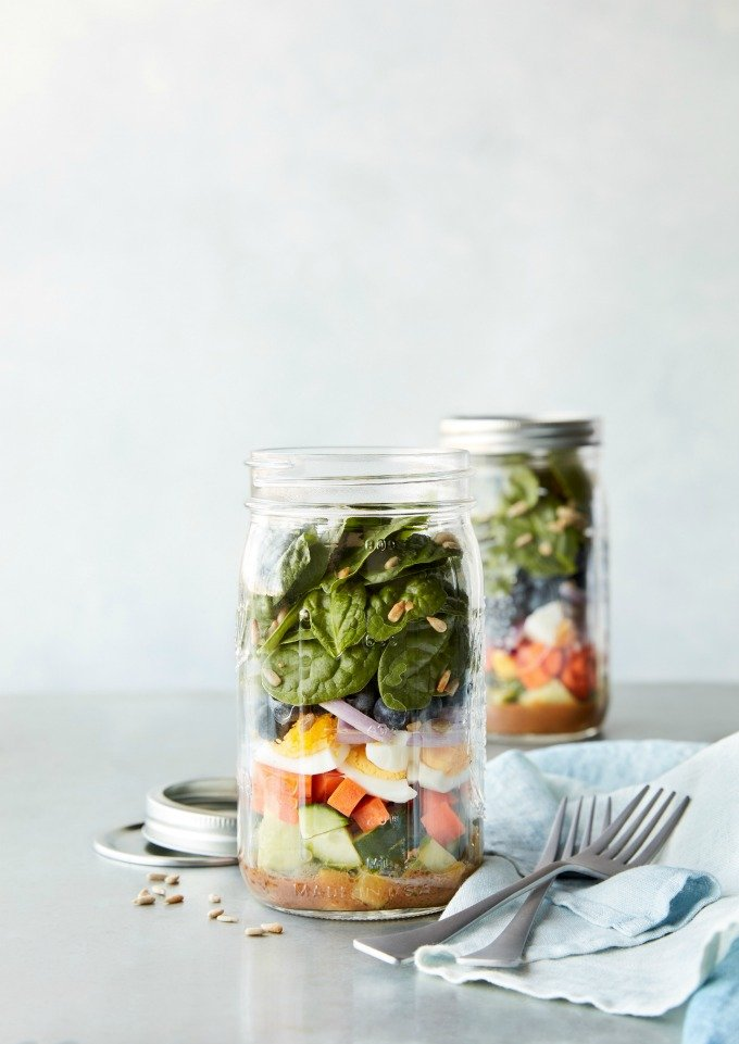 Mason jars with meal prepped salads, forks, and napkin
