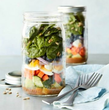 two superfood salads in jars with forks and a napkin