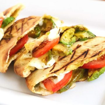 close up photo of 4 grilled pitas on a plate filled with tomato, mozzarella cheese, and avocado