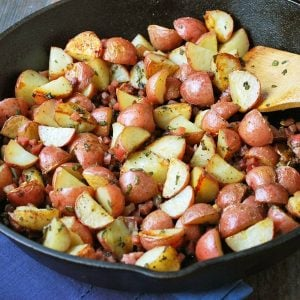garlic roasted potatoes in a cast iron skillet with a wooden spoon