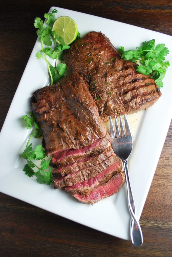 overhead photo of sliced flat iron steak on a white platter with herbs