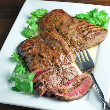 Sliced flat iron steak on a plate with fresh herbs