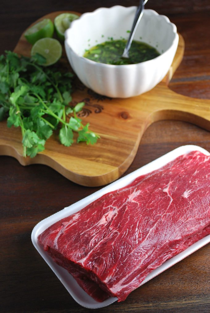 Uncooked flat iron steak with herbs and a bowl of marinade