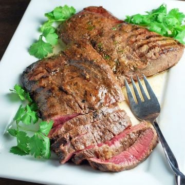 two flat iron steaks on a platter with half a steak sliced for serving. Fresh parsley and lime garnish the platter.