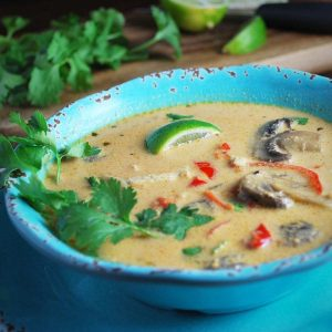 chicken curry soup with fresh lime, peppers, and mushrooms in a blue bowl garnished with fresh herbs