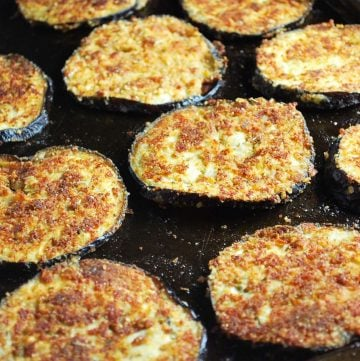 close up photo of breaded baked eggplant on a baking sheet