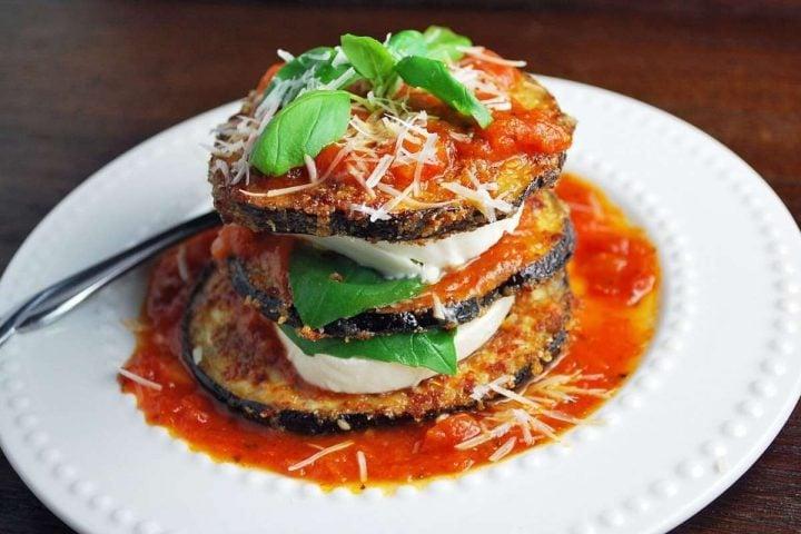 eggplant mozzarella stacks with fresh basil and marinara sauce on a plate