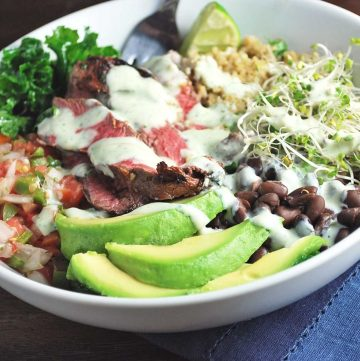 sliced avocado, steak, salsa, kale, black beans, quinoa, and bean sprouts in a bowl with a sauce