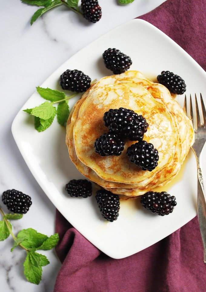plate of pancakes with berries and syrup with fork and napkin