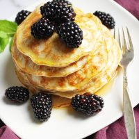 Protein blender pancakes on a plate with fresh blackberries and a fork
