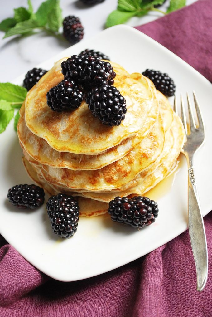 oat flour crepe-like pancakes on a plate with syrup and berries