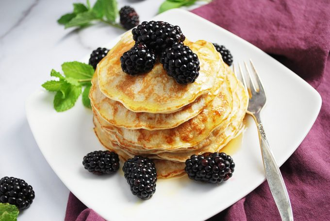 plate of pancakes with berries and syrup with a purple napkin and mint for garnish