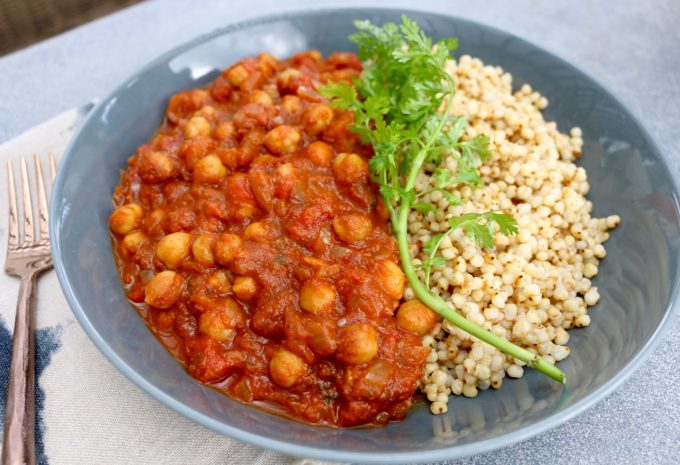 Chickpea curry in a bowl with couscous and fresh parsley
