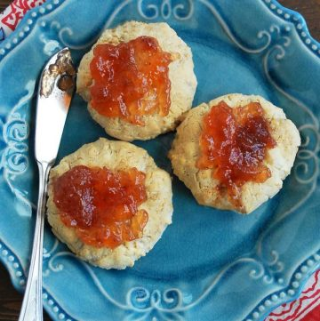 overhead photo of close up photo of 3 cookies on a plate topped with strawberry jam