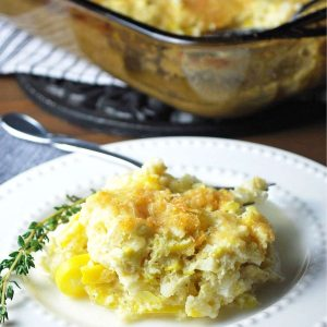 squash casserole on a plate with a sprig of thyme and a fork