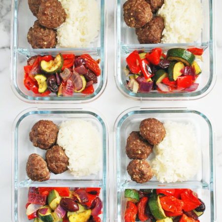 Glass meal prep containers with roasted vegetables, rice, and meatballs