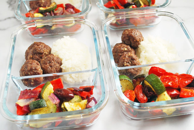 Meal prep containers with meatballs, rice, and roasted vegetables