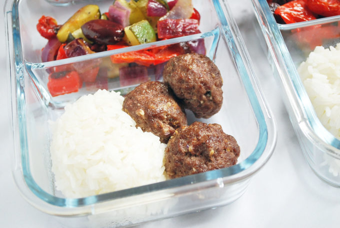 close up of meatballs, rice, and vegetables in a meal prep container