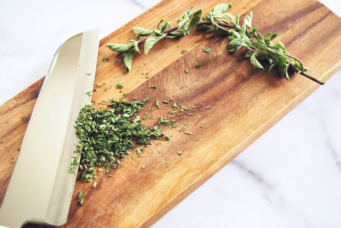 fresh herbs chopped on a wood cutting board