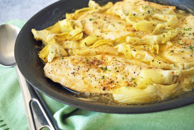 A close up of chicken breasts with artichokes and lemon in a skillet with a green napkin