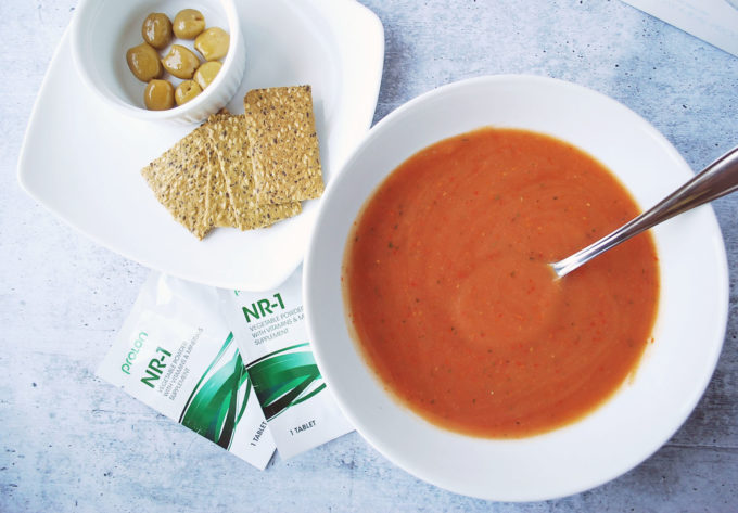 A bowl of soup and a spoon on a table, with crackers, olives, and packages of vitamins