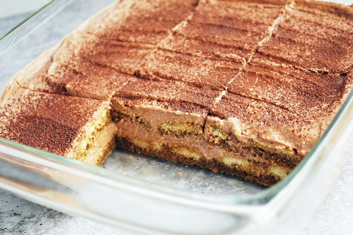 protein tiramisu in a glass dish with two slices cut out