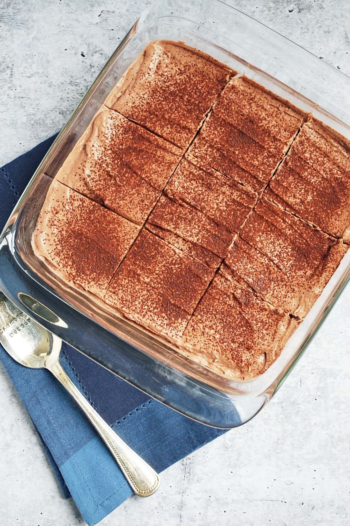 overhead photo of protein tiramisu in a glass dish with a spoon