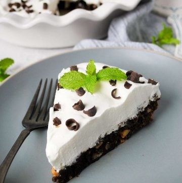 close up of a slice of chocolate pie with hazelnuts topped with cool whip, shaved chocolate and a fresh mint sprig