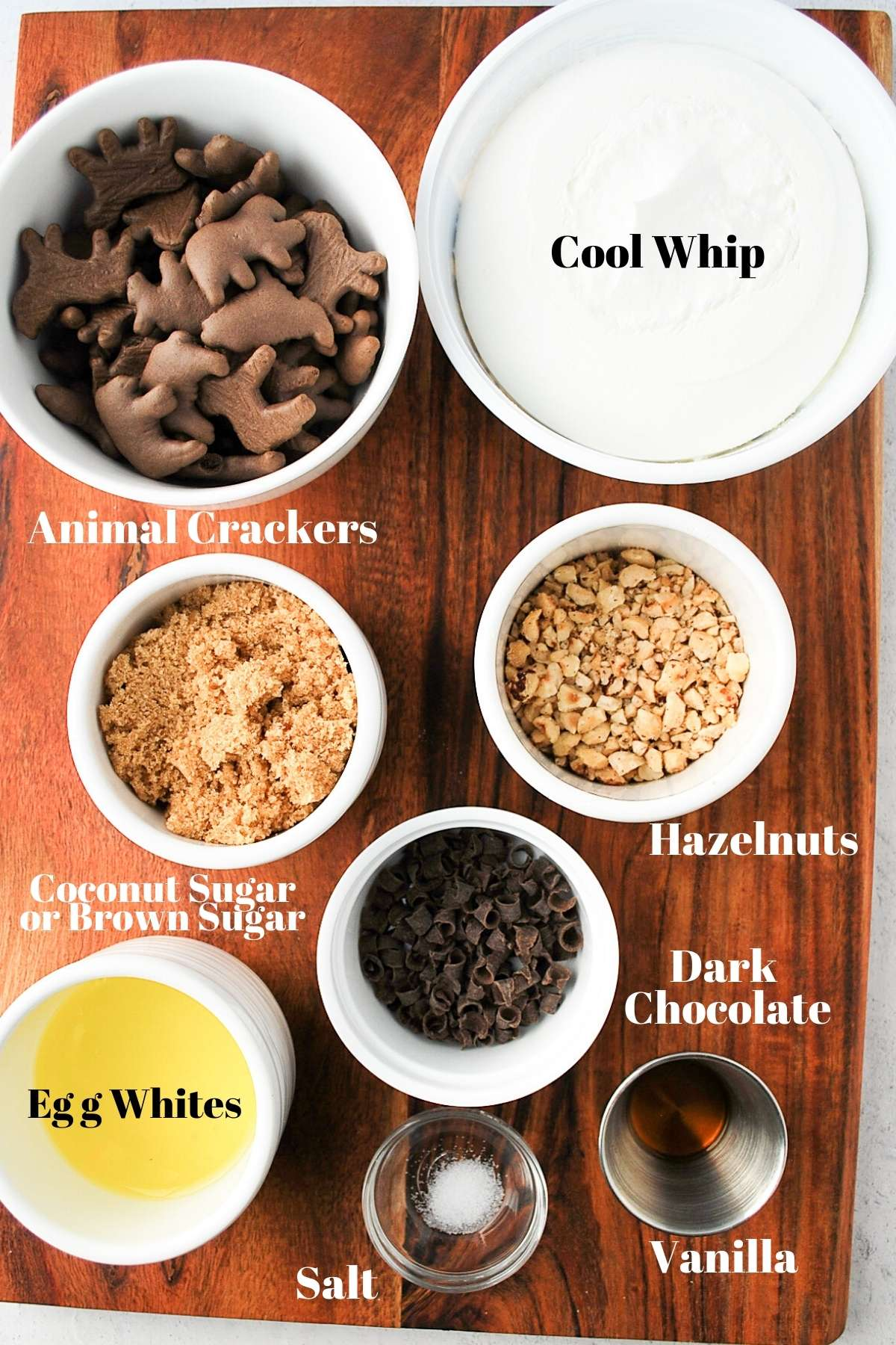 animal crackers, cool whip, sugar, nuts, shaved chocolate, vanilla, salt, and egg whites on a board for making pie