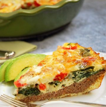 slice of quiche on a plate with avocado and a fork
