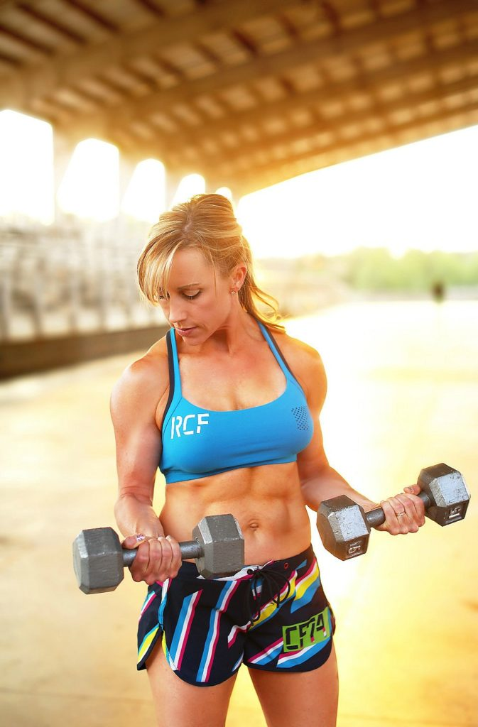 A woman standing curling dumbells