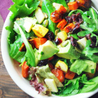 A bowl of salad with a purple napkin in the background