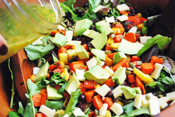 Drizzling vinaigrette on the best roasted vegetable salad