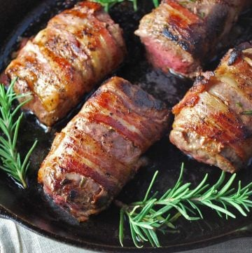 venison tenderloins wrapped in bacon seared in a cast iron skillet with fresh rosemary sprigs