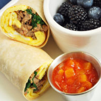 breakfast burrito sliced in half on a plate with salsa and berries