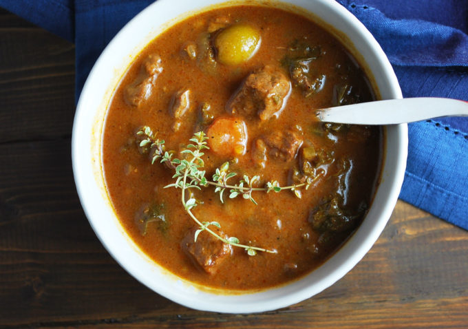 close up photo of a bowl of beef stew with fresh thyme on top