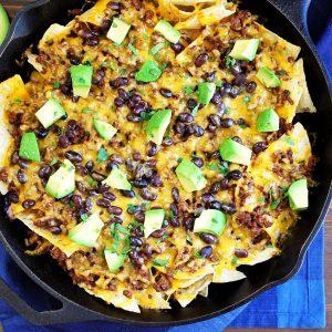 overhead photo of a skillet of nachos next to a blue napkin