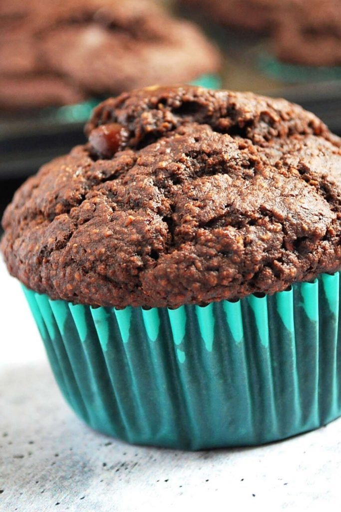 close up of a chocolate muffin in a blue cupcake liner