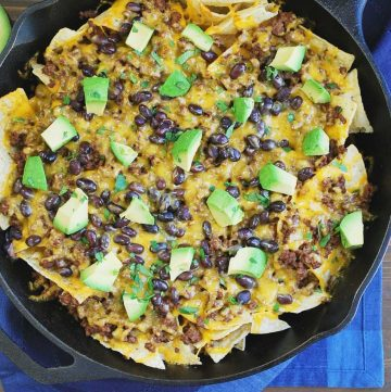 nachos topped with beef, black beans, cheese and avocado in a cast iron skillet