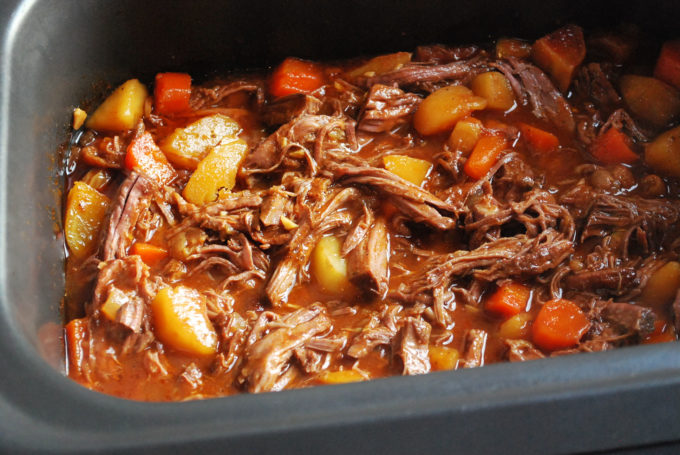 Cooked shredded beef with vegetables and spices in a slow cooker