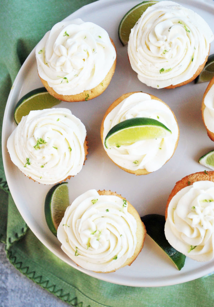 Overhead photo of a platter of key lime cupcakes with lime slices and zest