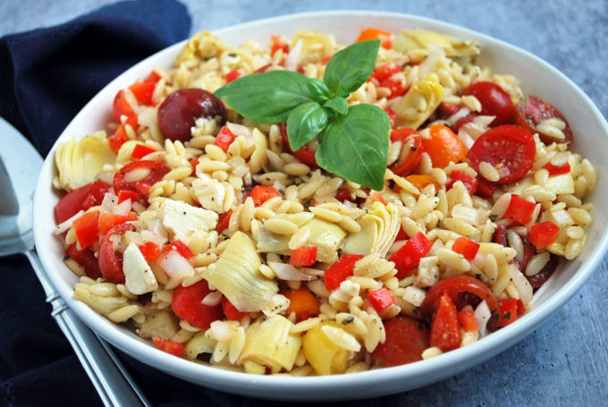 Mediterranean orzo pasta salad with tomatoes, artichokes, peppers and onion with a sprig of basil on top