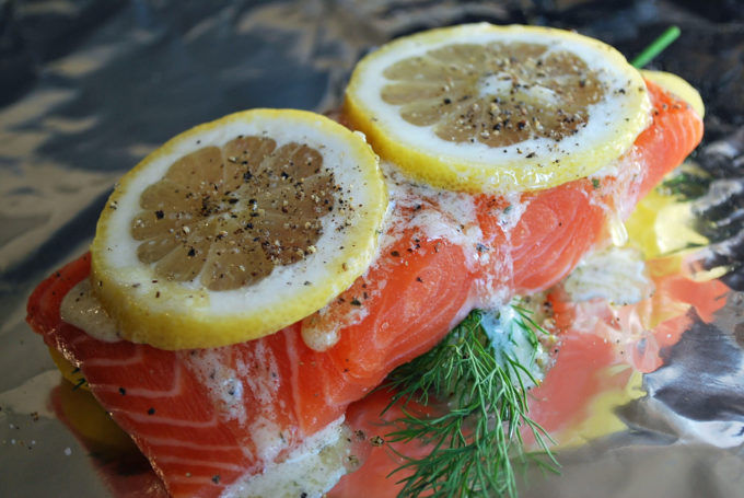 wild salmon topped with lemon, herbs and butter in foil ready to grill
