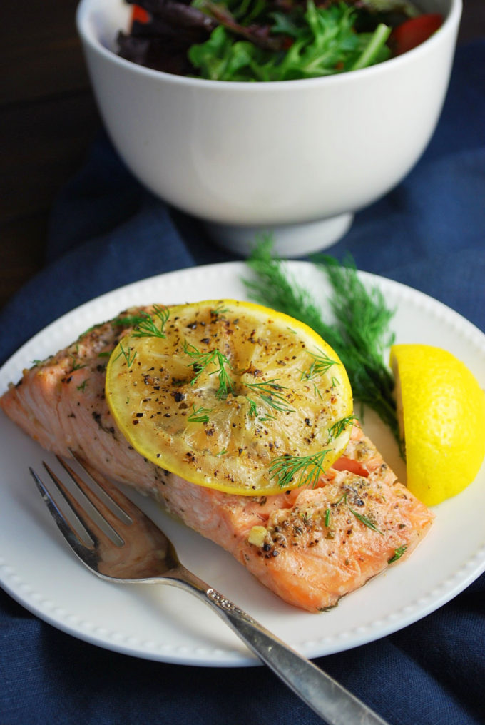 Grilled salmon on a plate topped with lemon served with a bowl of greens