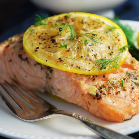 foil packet grilled salmon on a plate with a fork